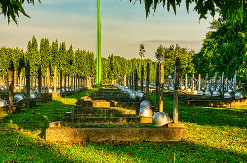 Various tombstones with military hardhats located on grassy ground in national main heroes cemetery against green trees and tall structure