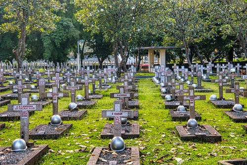 Abundance of tombstones with crosses and military helmets located on grassy ground on national main heroes cemetery with structure