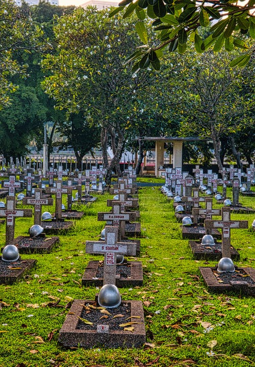 Gravestones with military helmets located on grassy ground in national cemetery with lush tall plants and structure in Kalibata in Indonesia