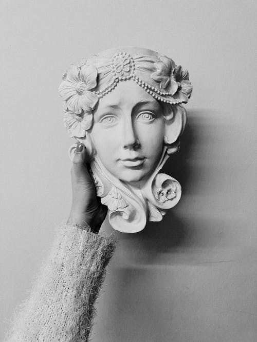 Black and white of crop unrecognizable female in warm clothes demonstrating handicraft plaster sculpture