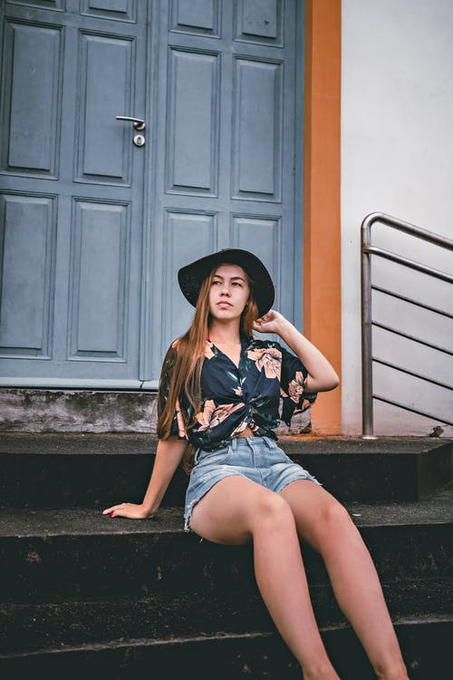 Young contemplative female tourist in denim shorts and hat looking away from city staircase against entrance door