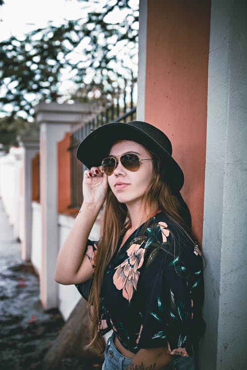 Side view of self assured young lady with long hair in stylish outfit adjusting sunglasses while standing near aged residential house on street