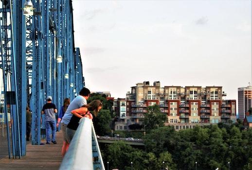 People Looking Down A Bridge