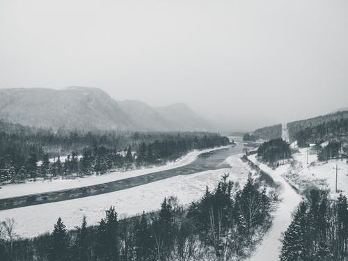 Black and white of picturesque scenery of frozen river flowing through snowy mountainous valley near coniferous forest against foggy sky