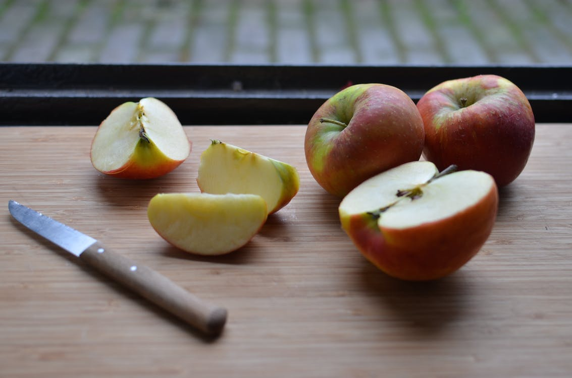 Board with slices of fresh apples and knife near window
