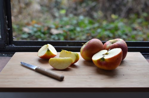High angle of cut red apples placed on wooden cutting board with knife near window