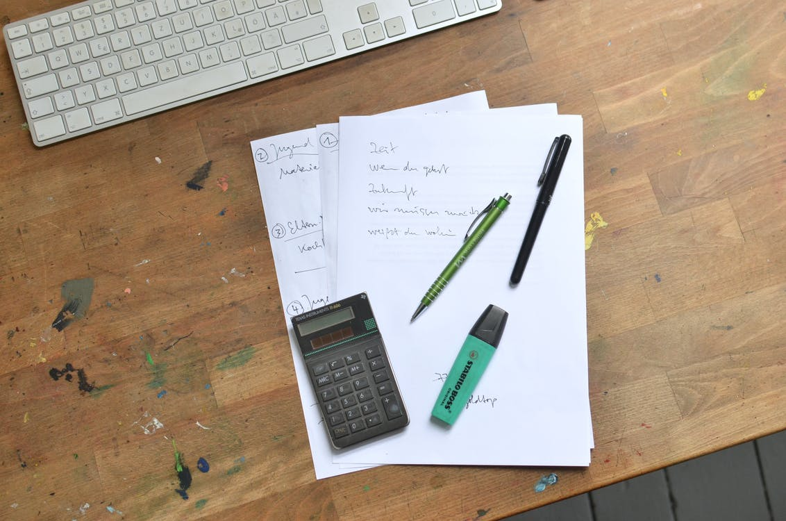 Black and Gray Calculator Beside White Printer Paper