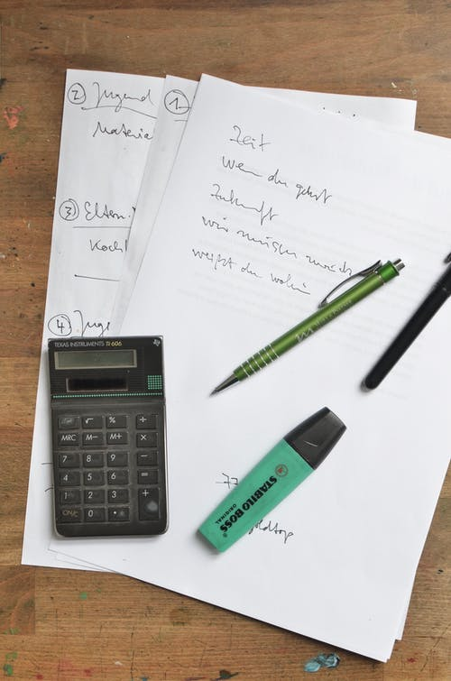 Calculator and stationary on paper sheets on table