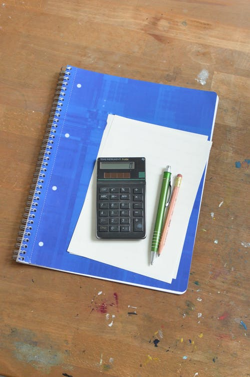 Overhead of pen and pencil near calculator placed on notebook with blue cover and paper sheet on shabby wooden table with paint spots