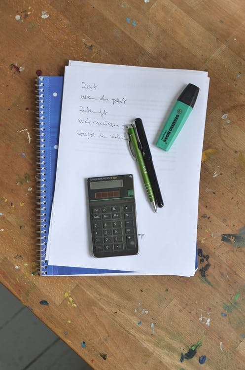 Overhead view of pens and calculator placed on paper sheet with notes on notebook