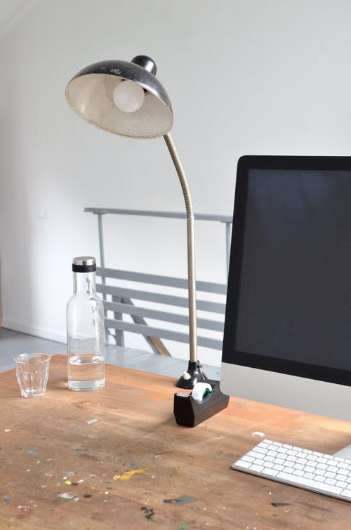 Computer and lamp on table in office