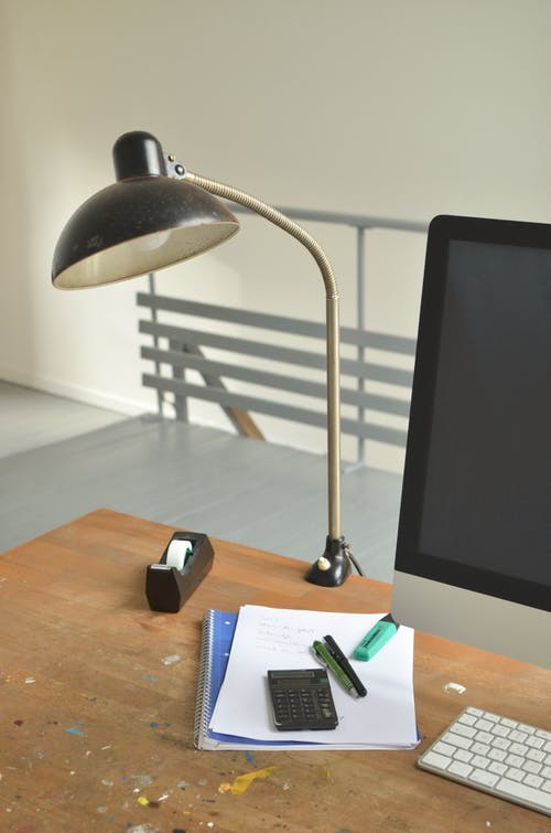 High angle of wooden table with Monitor and keyboard lamp papers and office supplies on workplace