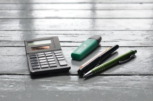 Calculator and pens on wooden desk