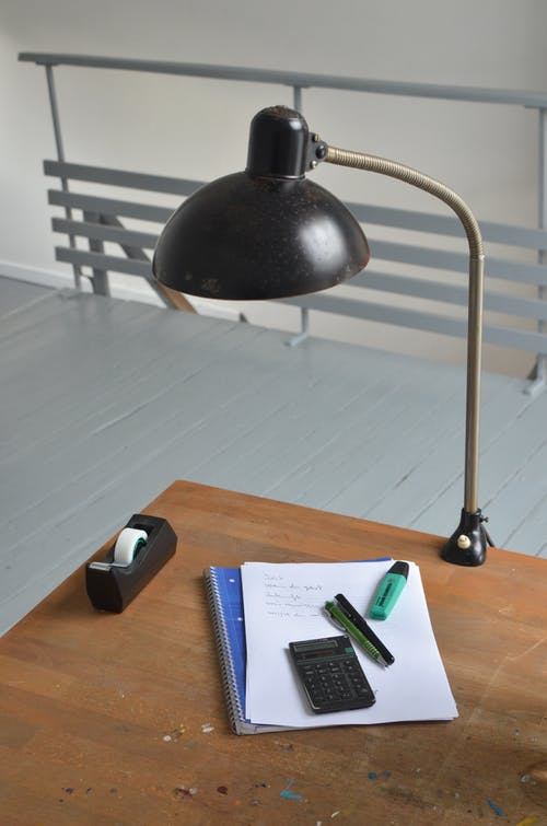 From above of wooden table with lamp papers calculator and sellotape in dispenser on workplace