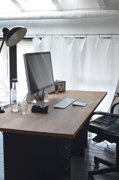 Office table with big monitor keyboard lamp and stationeries and chair in modern workplace