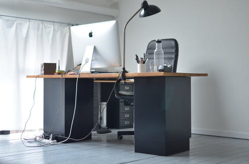 Low angle of office table with big monitor stationeries and bottle with beverage in modern workplace