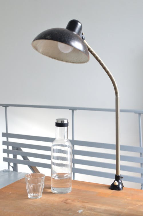 Old fashioned lamp with glass and bottle of water placed on wooden table