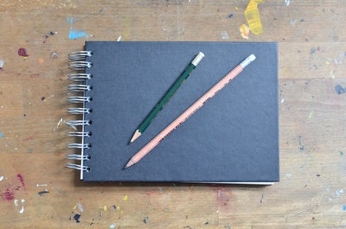 Top view of blank black notepad with pencils placed on shabby wooden surface stained with colourful paints