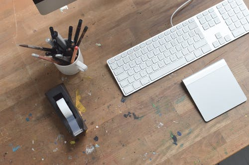 From above of artist workplace with modern keyboard and stationary placed on wooden desk stained with paint