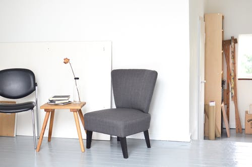 Chairs and table placed near white wall in modern workshop