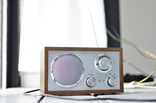 Classic styled radio receiver with chrome buttons and speaker and wooden case placed on table in daylight