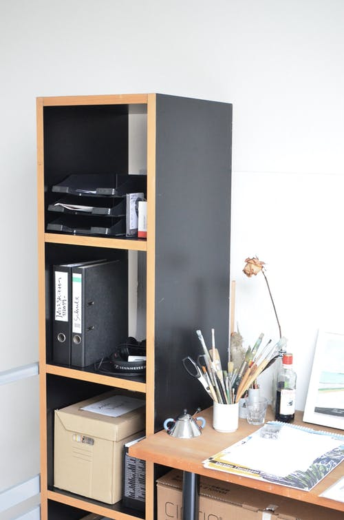Various documents folders and box placed on wooden shelves near table with assorted stationery in modern office