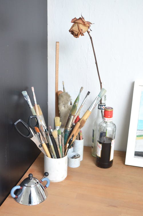 From above of various paintbrushes with scissors and pencils placed in cup arranged on wooden table near dry rose in glass vase in creative art studio