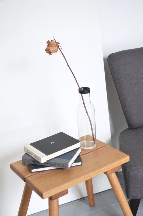 High angle of dry flower in simple glass vase placed on small wooden table with stack of books near armchair in light room