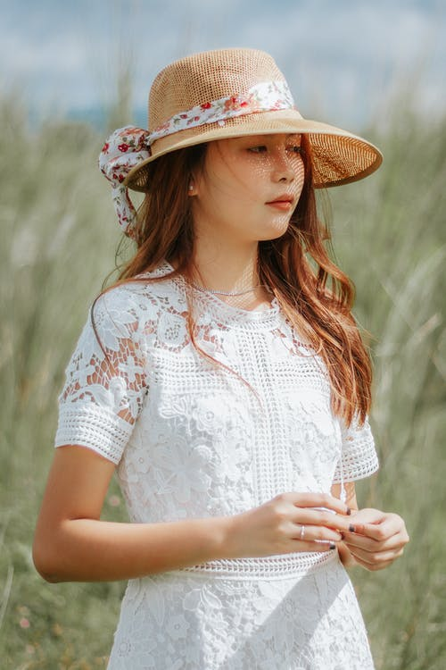 Thoughtful Asian female wearing elegant dress and straw hat standing among tall grass in countryside