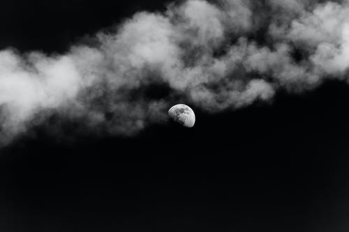 Black and white of shining moon on dark gloomy sky with clouds of smoke