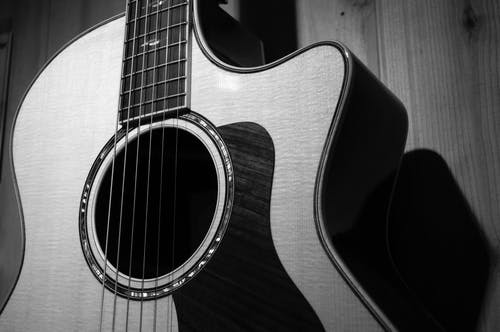 Acoustic Guitar in Grayscale Photo