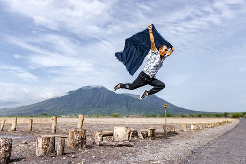 Man in Blue and White Long Sleeve Shirt and Black Pants Jumping on Brown Wooden Post