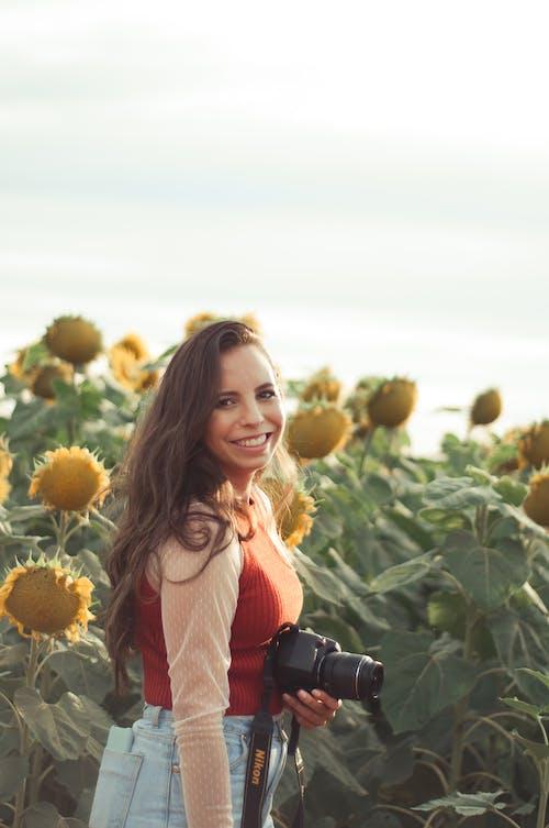 Happy photographer standing in sunflower field