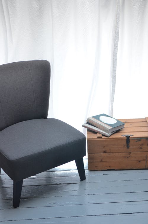 Comfortable gray seat with soft cushion standing on blue wooden floor near nightstand with books on top in light room