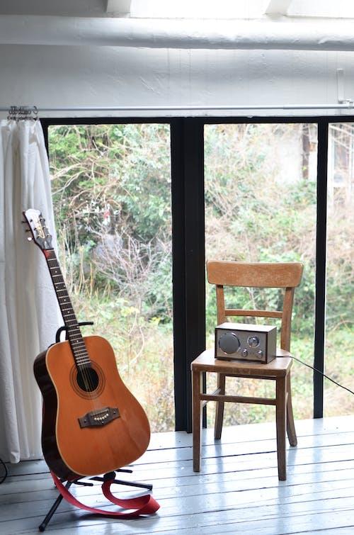 Guitarra Acústica Marrón En Silla De Madera Marrón