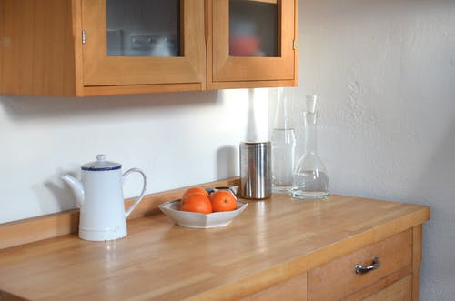 Kitchen counter with utensils under hanging cupboard