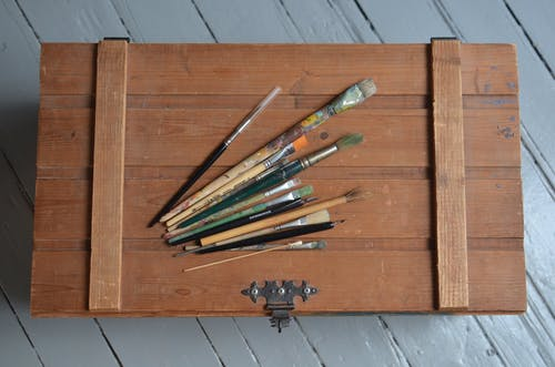 From above of various brushes placed on old fashioned chest box made of wood on light blue floor