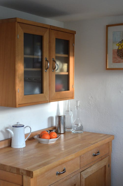 Kitchen counter with different utensils and cupboard for dishes