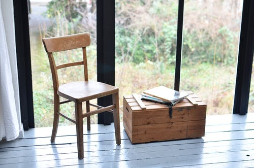 Seat made of wood and low old fashioned box with stack of books placed in front of wide window in modern room