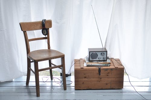 Chair and vintage box with radio set in light room