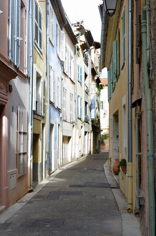 Paved narrow empty walkway between old small multicolored buildings in town at daylight in summer