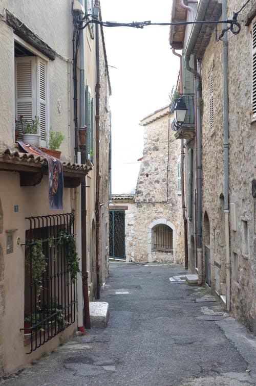 Narrow alley between aged houses in city