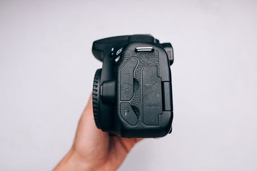 Black Dslr Camera on Persons Hand