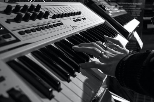 Person Playing Electric Piano in Grayscale Photo