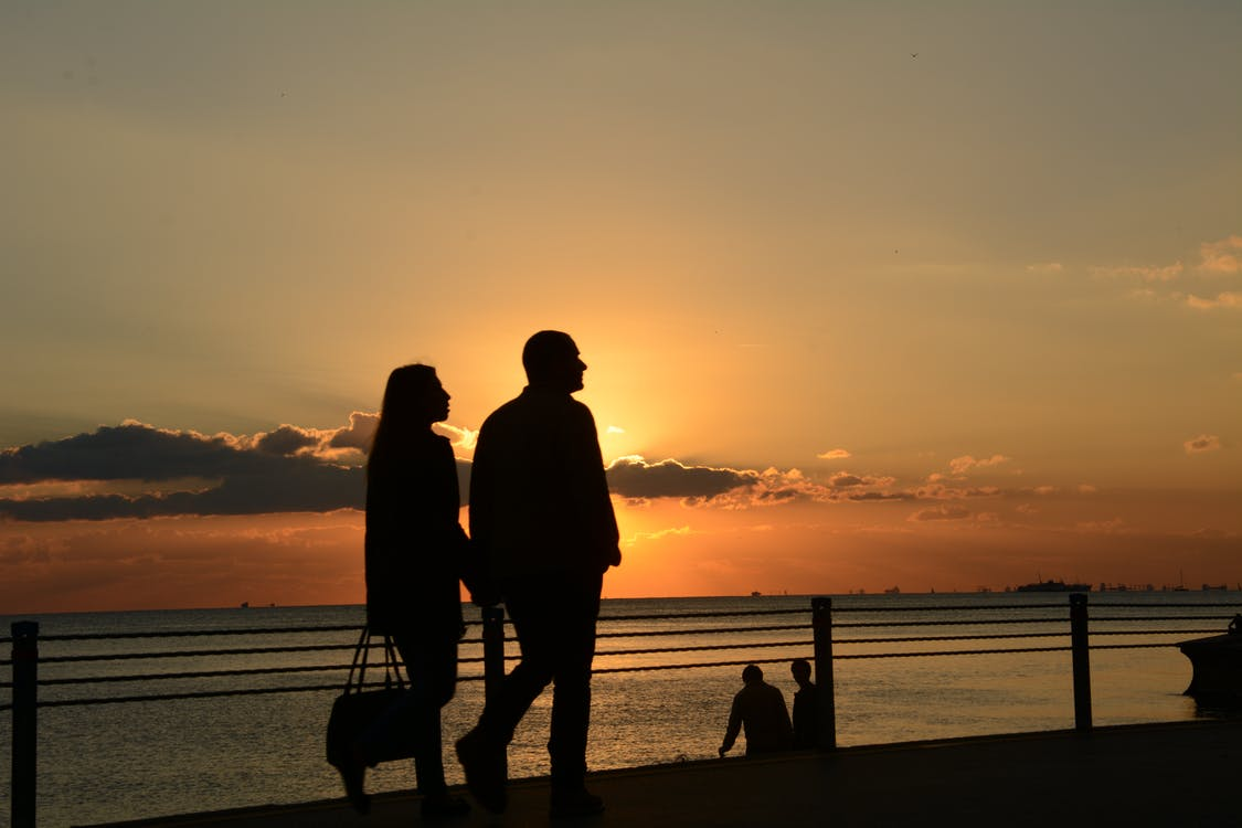Man and Woman Silhouette Walking during Sunset