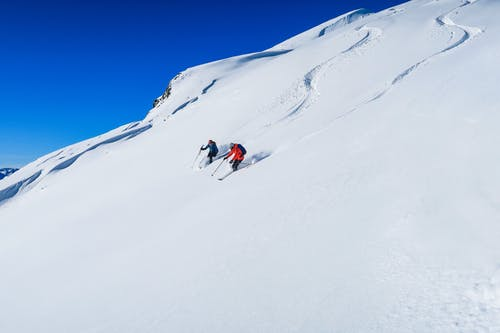 Anonymous skiers in warm clothes riding down on snowy stiff mountain slope beneath clear blue sky on sunny winter day