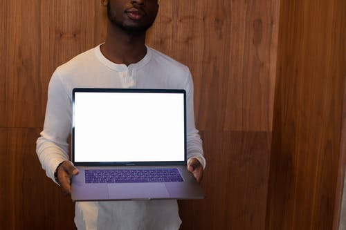 Man in White Crew Neck Shirt Holding White Laptop Computer