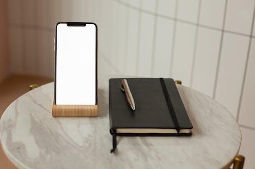 Black Hardbound Book on Brown Wooden Table