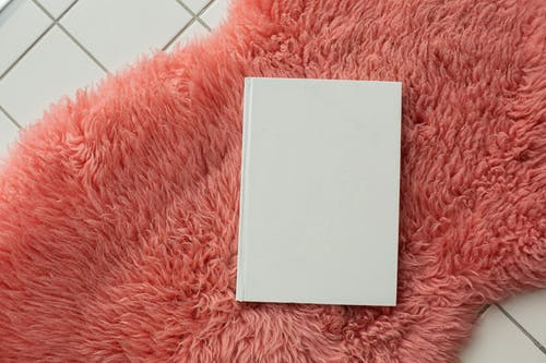 Blank white notebook placed on pink carpet
