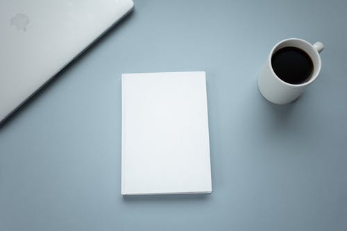 Top view of closed laptop placed near mug of hot americano and white hardcover book on table